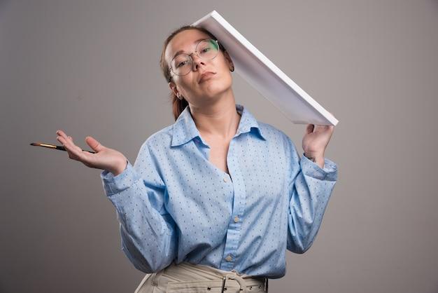Mulher de óculos segurando uma tela e um pincel em fundo cinza. foto de alta qualidade