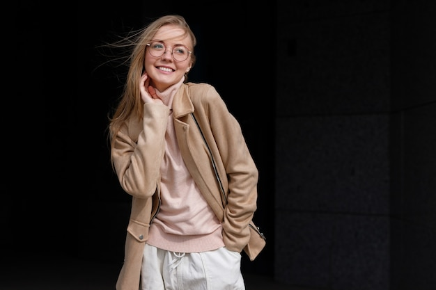 Mulher de óculos sorrindo feliz contra um fundo escuro