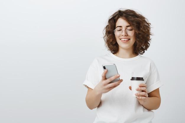 Mulher de óculos sorrindo para a mensagem de texto do celular, bebendo café no intervalo do escritório