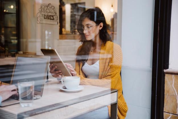 Mulher de óculos usando tablet no café
