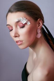 Mulher de olho maquiagem primavera com flores brancas.