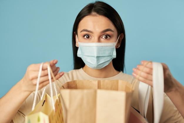 Mulher de olhos abertos posando com uma máscara médica e segurando sacolas de compras no estúdio