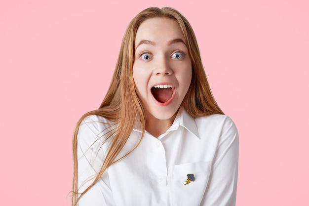 Mulher de olhos azuis espantada com expressão animada chocada, mantém a boca aberta, recebe notícias inesperadas, isoladas na parede rosa. pessoas, emoções, conceito de reação