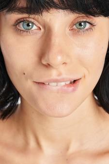 Mulher de olhos azuis mordendo o lábio