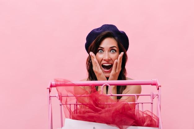 Mulher de olhos azuis na boina preta olha para a câmera surpresa no fundo rosa. feliz linda garota com cabelo escuro, posando no isolado.