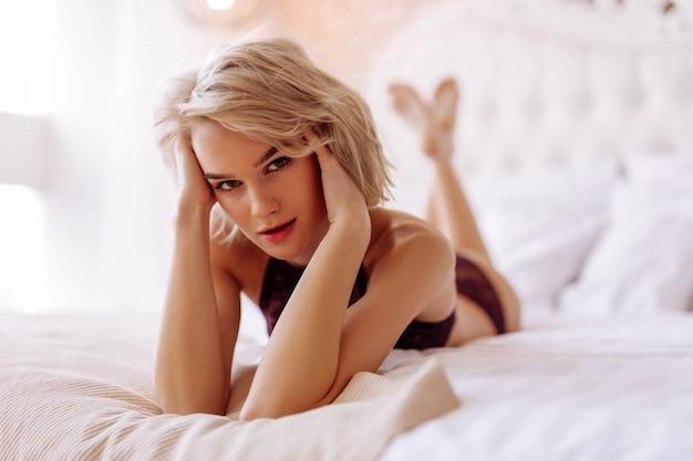 Mulher de olhos escuros. mulher de olhos escuros e rosto bonito se sentindo aliviada relaxando na cama no fim de semana
