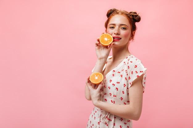 Mulher de olhos verdes com cabelo ruivo encara com espanto a câmera e segura laranjas suculentas no fundo rosa.