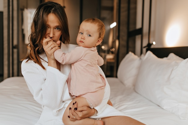Mulher de olhos verdes em roupão de banho beija a mão de seu filho. mãe e filha posam em casa sentadas na cama.