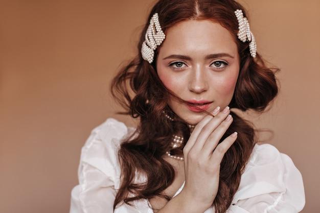 Mulher de olhos verdes toca coquete no cabelo. mulher em roupa branca e acessórios de pérolas parece para a câmera.