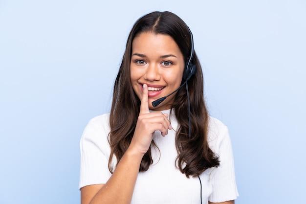 Mulher de operador de telemarketing trabalhando com um fone de ouvido sobre parede isolada
