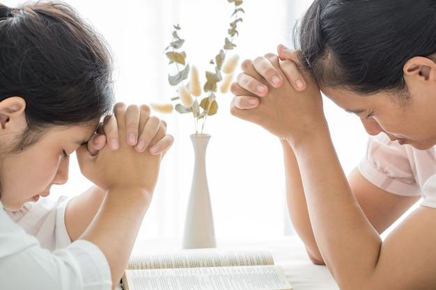 Mulher de oração adora a deus e ora de casa pelo coronavírus covid-19. ore em casa, igreja online, orando com as mãos, adoração em casa