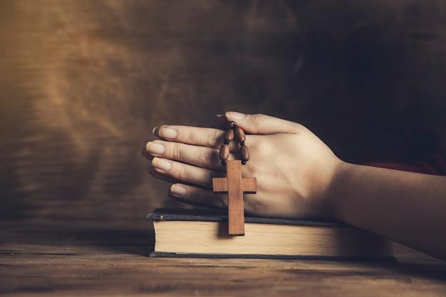 Mulher de oração segurando uma cruz na bíblia
