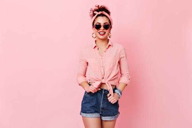 Mulher de ótimo humor está posando no espaço rosa. garota de óculos escuros e brincos de ouro, vestida com camiseta e shorts, está sorrindo.