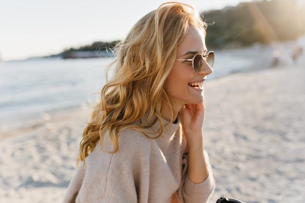 Mulher de ótimo humor gosta de dia ensolarado de primavera no mar. blinde em traje de caxemira segurando uma xícara de chá.