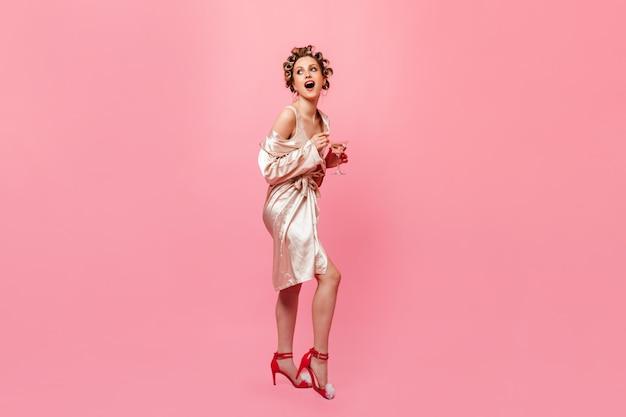 Mulher de ótimo humor posando com taça de champanhe na parede rosa