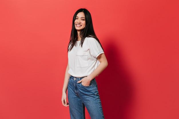 Mulher de ótimo humor, posando na parede vermelha