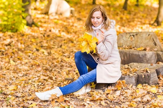 Mulher de outono em folhas de fundo na floresta