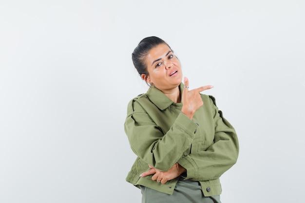 Mulher de paletó, camiseta apontando para o lado direito e parecendo confiante