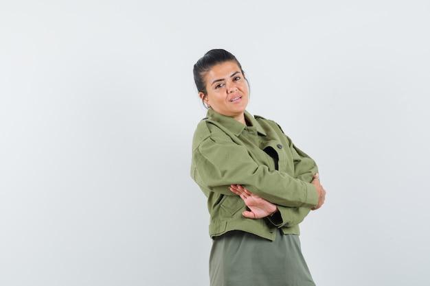 Mulher de paletó, camiseta em pé com os braços cruzados e parecendo confiante