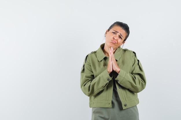 Mulher de paletó, camiseta mostrando gesto namastê e parecendo inocente