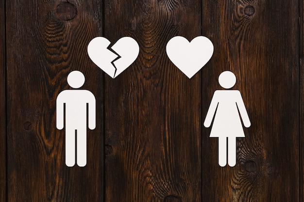 Mulher de papel com coração e homem com coração partido na madeira