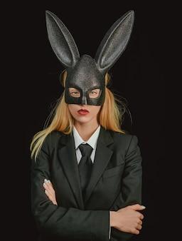 Mulher de páscoa. mulher sexy com máscara de coelho da páscoa em um fundo preto e parece muito sensual.