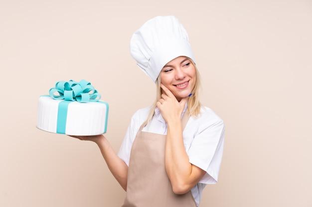 Mulher de pastelaria segurando um bolo