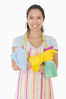 Mulher de pé com os braços cruzados segurando produtos de limpeza