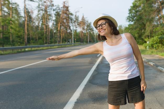 Mulher de pé de chapéu na estrada parando o carro
