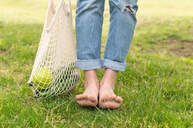 Mulher de pé descalço close-up e saco reutilizável