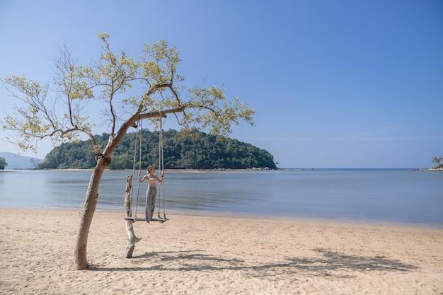 Mulher de pé em um balanço, na praia.