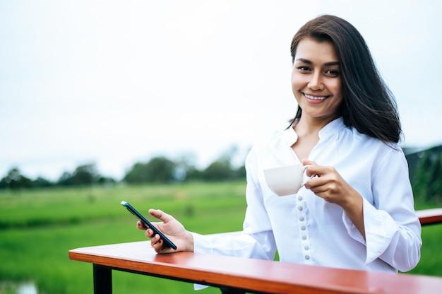 Mulher de pé em um smartphone e segurando uma xícara de café
