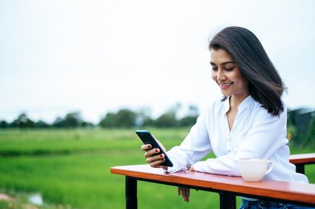 Mulher de pé em um smartphone e tomar uma xícara de café