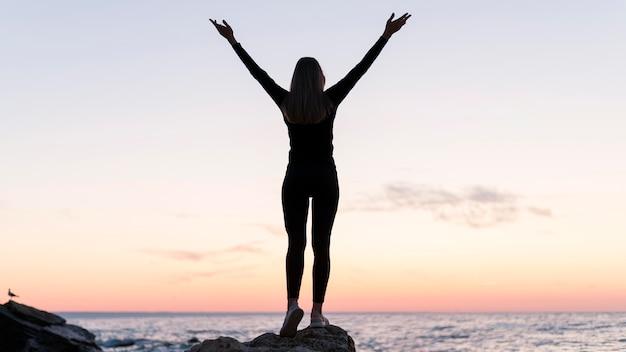 Mulher de pé na costa com os braços para cima