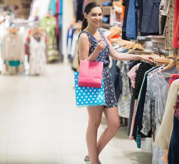 Mulher de pé na cremalheira de roupas segurando dois sacos