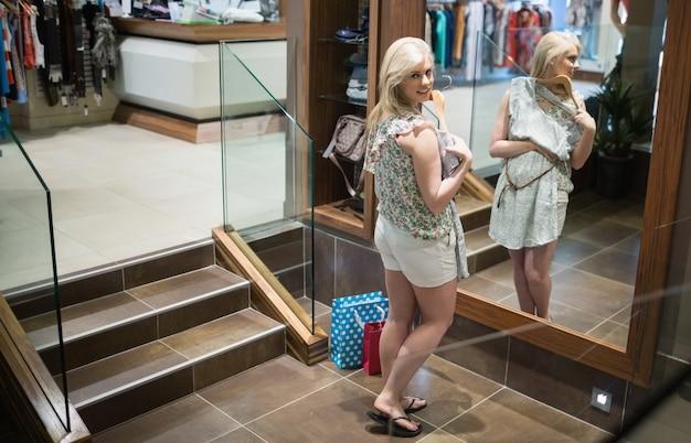 Mulher de pé na frente do espelho, sorrindo