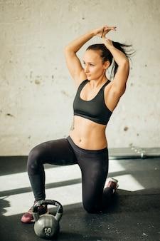 Mulher de pé no joelho e se preparando para o exercício de ajuste cruzado