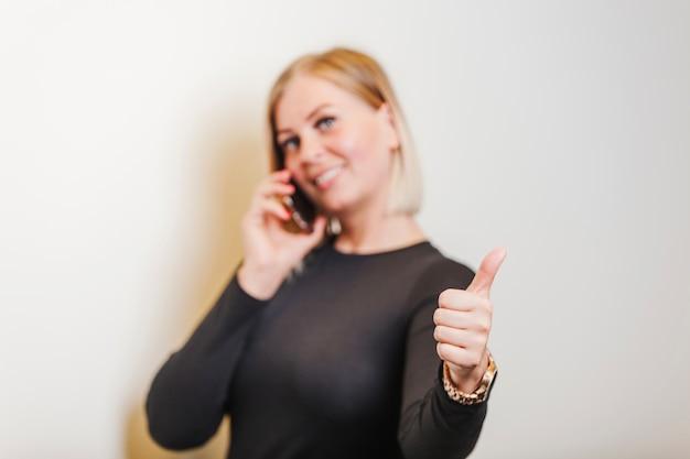 Mulher de pé segurando o telefone dando o polegar para cima