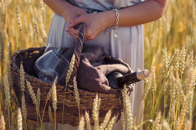 Mulher de pele bronzeada, lindo vestido prateado em um piquenique em um campo de centeio, cesta com vinho e copos