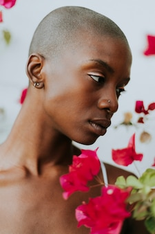 Mulher de pele clara rodeada por flores vermelhas