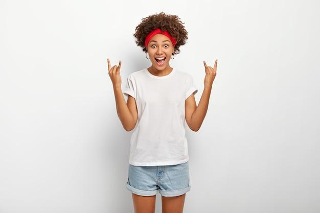 Mulher de pele escura alegre animada parece com alegria para a câmera, mostra o gesto de heavy metal rock n roll, vestida com roupa casual, isolado sobre fundo branco. linguagem corporal.