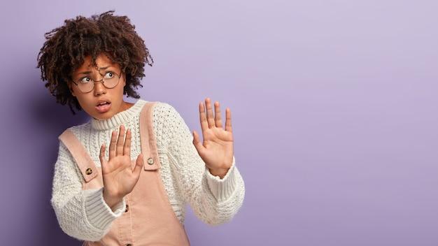 Mulher de pele escura assustada estende as palmas das mãos, faz gesto de proteção, preocupa-se com expressão facial nervosa, pede para não se aproximar, usa óculos ópticos e macacão, isolada na parede roxa