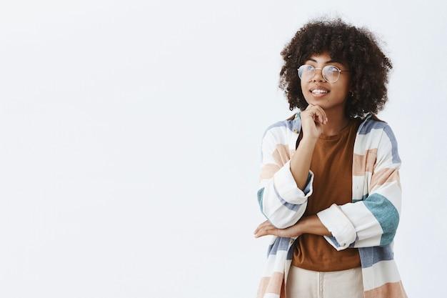 Mulher de pele escura atraente artística, elegante e criativa com óculos transparentes e roupa da moda em pose pensativa, olhando para o canto superior esquerdo com a mão no queixo pensando