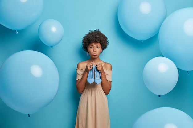 Mulher de pele escura chateada com cabelo encaracolado segura sapatos de salto alto azul, se prepara para poses de festa contra balões azuis.