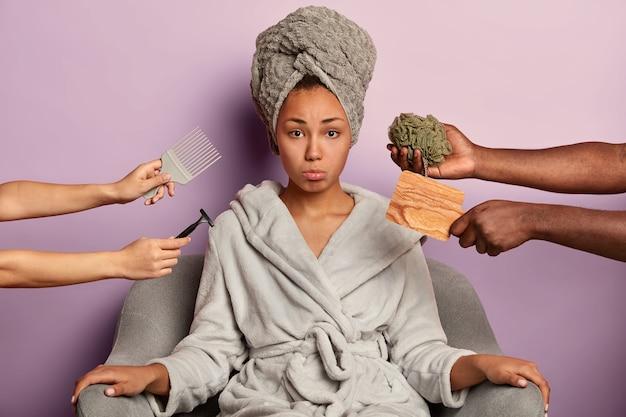 Mulher de pele escura chateada, de roupão e toalha, ocupada com procedimentos de higiene