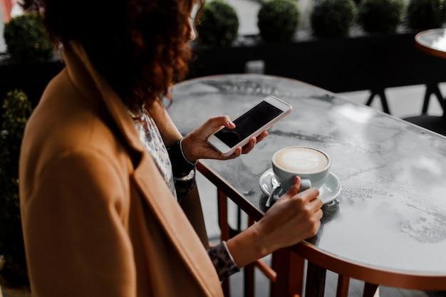 Mulher de pele escura com penteado afro, verificando seu feed de notícias ou mensagens através de redes sociais