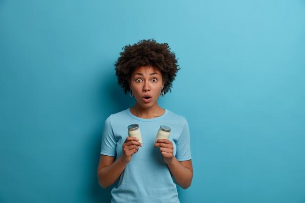 Mulher de pele escura emocional assustada engasga com o choque, mantém o queixo caído, segura dois copos de iogurte, tem nutrição saudável, mantém a dieta saudável, usa camiseta azul casual. pessoas, emoções, estilo de vida