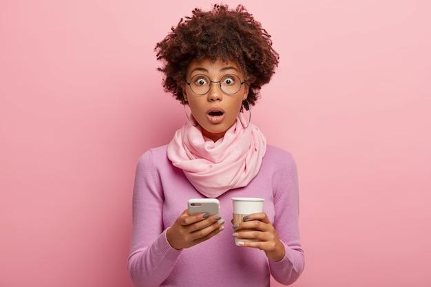 Mulher de pele escura, emocional e estupefata, com cabelo afro encaracolado, verifica o e-mail no dispositivo smartphone