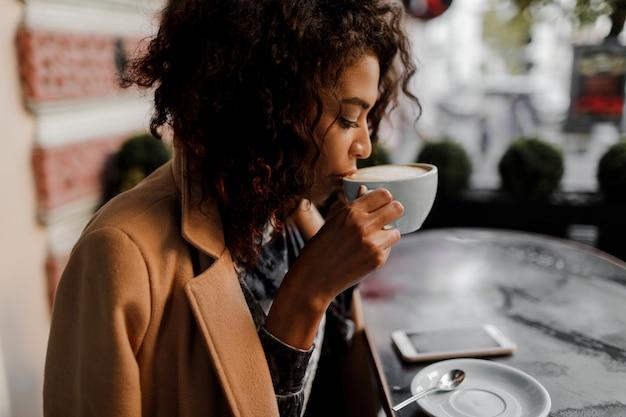 Mulher de pele escura hipster entusiasta com penteado afro, verificando seu feed de notícias