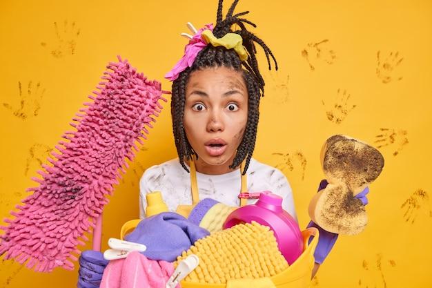 Mulher de pele escura impressionada sem palavras penteada tranças, olhares com expressão omg limpa tudo, água suja, equipamento de limpeza lava isolado sobre parede amarela